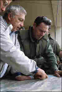 Israeli armed forces Brig. Gen. Amos Yaron and Sharon study a map.