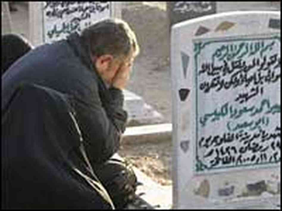 A man in Fallujah weeps at the grave of his loved one