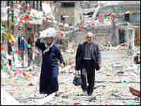 An elderly Lebanese couple carry bags as they leave the southern border town of Bint Jbail.