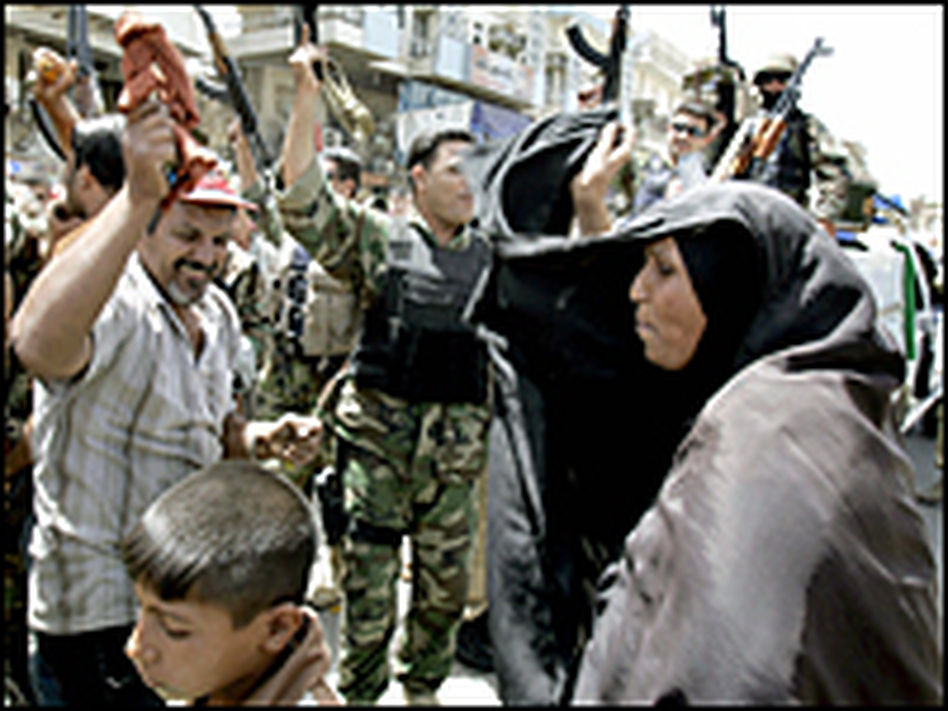 Iraqis dance with soldiers in Baghdad after hearing Iraqi Prime Minister Nuri al-Maliki announce the death of al-Qaida leader in Iraq Abu Musab al-Zarqawi, June 8, 2006.