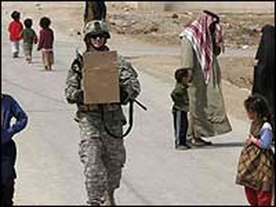 A U.S soldier carries a box of goodies for distribution to children while on a routine patrol.