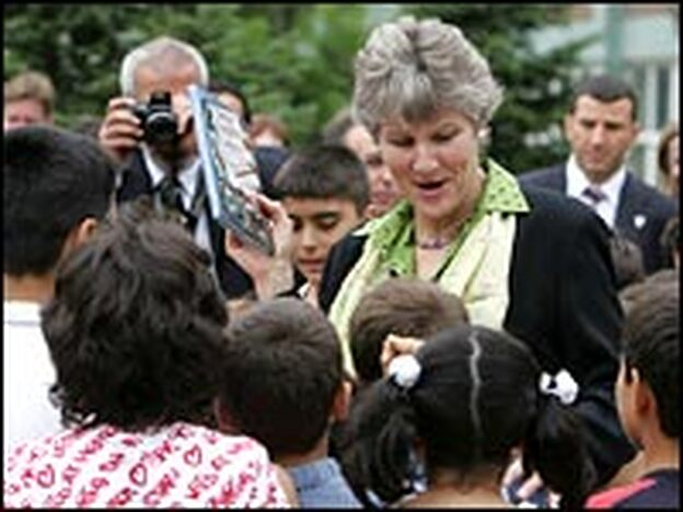 Undersecretary of State for Public Diplomacy Karen Hughes hands out books to Turkish students in Istanbul during a regional tour aimed at improving America's image abroad, Sept. 28, 2005.