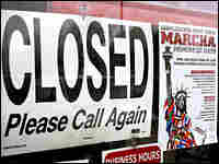 """A store displays its closed sign Monday, next to a promotional poster for the """"Marcha"""" in Spanish."""