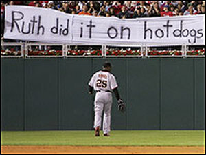 Barry Bonds walks to left field as a sign reads: 'The Babe did it on hot dogs.'