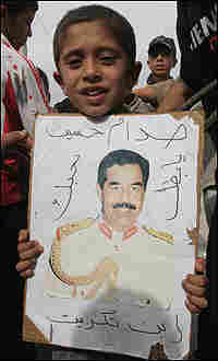 A boy in Tikrit carries a portrait of Saddam.