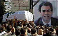 Mourners carry the coffin of Pierre Gemayel past his portrait in his hometown of Bikfaya.