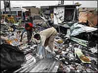 Iraqi shop owners search for their belongings at the site of a car bomb in Baghdad's Sadr City