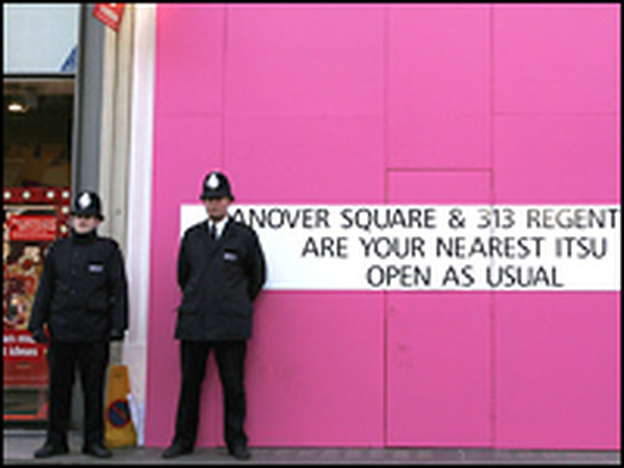 British police officers stand outside of a boarded-up Itsu restaurant in London. Detectives are continuing to examine five locations in London where traces of polonium-210 were found.