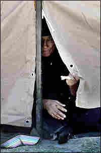 An elderly Shiite Iraqi woman peers from her tent at a camp for displaced people north of Baghdad.