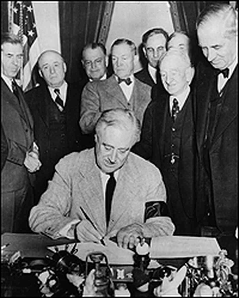FDR signs a declaration of war as members of Congress look on.