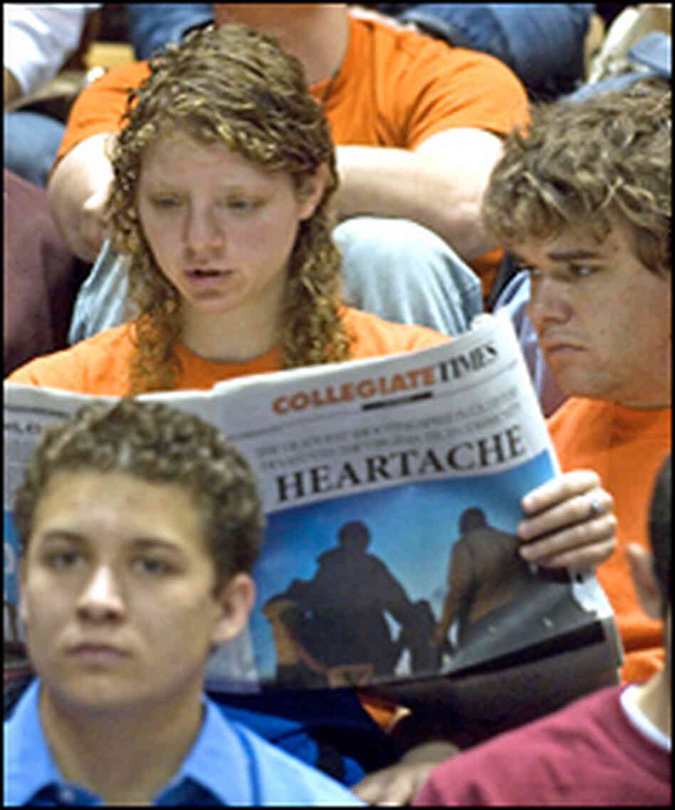 Students read their school newspaper prior to a convocation and memorial.