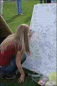 Memorial boards stand outside Norris Hall at Virginia Tech. A woman records her thoughts.
