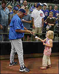Lou Piniella signs an autograph for a small girl.