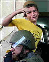 A young Jewish settler cries as he is carried by an Israeli police officer/AP.