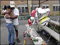 Two mourn the three killed in Newark, N.J., at an impromptu memorial/AP.