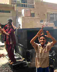 Iraqi youths jubilate at the scene where a roadside bomb targeted an interior ministry forces convoy