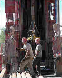 Workers prepare metal casings for 8 5/8 inch drill rig outside the Crandall Canyon Mine.