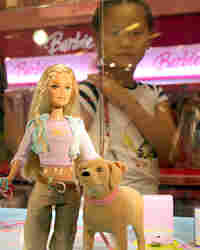 A girl in Shanghai looks at a Barbie and Tanner toy set, made by Mattel, which is still for sale.