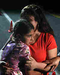 Maria Lerma hugs her daughter Adilene as they wait to hear news about her husband, Natalio.