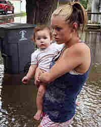 Jessica Ross walks through flood water with her daughter, Savannah, near their home in Fox Lake, Ill