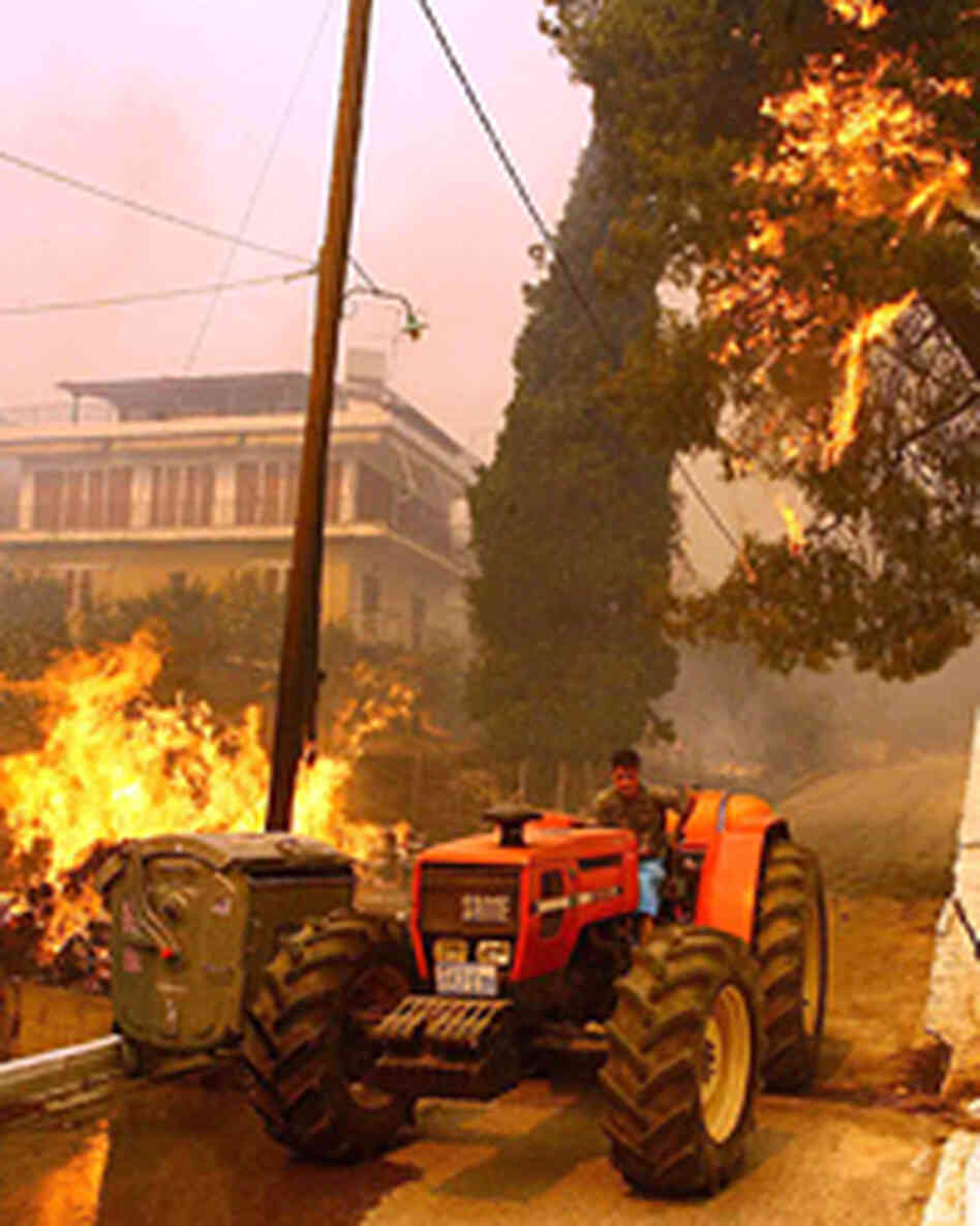 A man drives a tractor past burning vegetation in Platanos, near the site of Ancient Olympia.