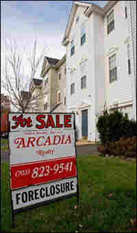 A sign advertises that a home for sale is in foreclosure.