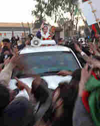 Benazir Bhutto waves from her car just seconds before being attacked.