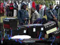 Kenyans watch as police guard ballot boxes.