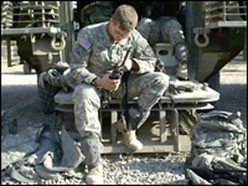A U.S. soldier from the 5-20 Infantry Division cleans his rifle on the ramp of his Striker.