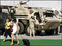 Two women walk past tanks as they attend the opening of the IDEX exhibition in Abu Dhabi.