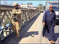 A British soldier patrols in Basra, walking alongside a local citizen.