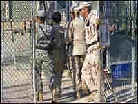 A detainee is led back to his cell at Camp Delta.