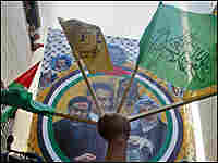 Hamas and Fatah flags are raised during a rally to celebrate the 42 years of the Fatah founding.
