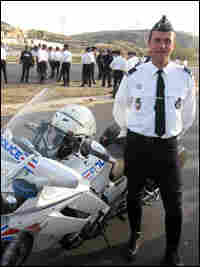 Christian De Larrain stands next to a police motorcycle.