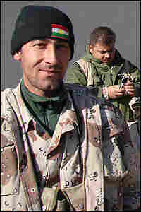 A Kurdish soldier proudly wears a wool cap with the flag of Kurdistan on it.