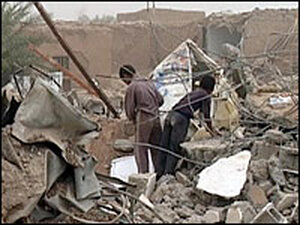 Iraqis inspect destruction at the site of a truck bomb blast in the village of Armili.