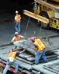Construction workers remove faulty tiles at the mouth of the I-90 Connector in Boston