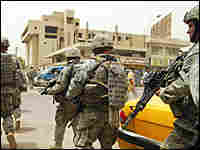 U.S. soldiers walk past an Iraqi boy as they patrol in central Baghdad.