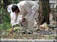 A Pakistani investigator collects evidence from a bomb blast site in Islamabad.