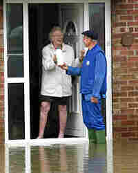 A milkman delivers milk to a flooded home Monday in Tewkesbury, Gloucestershire, England.