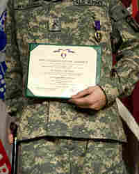 Pfc. Christopher Williams holds a certificate during a June Purple Heart ceremony in Washington.