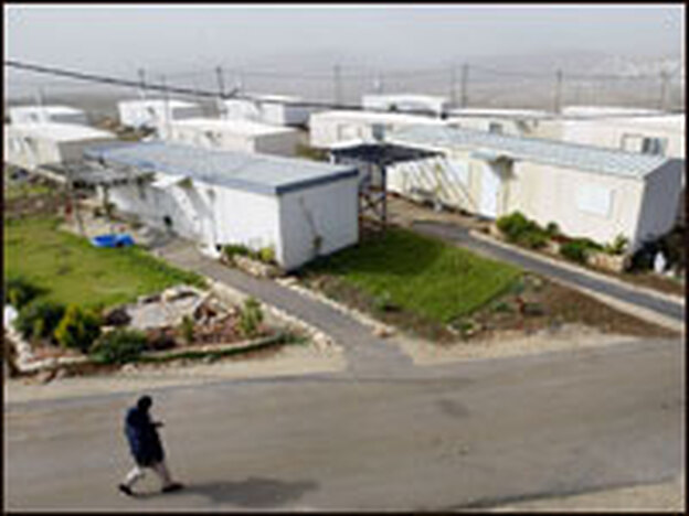 An armed Jewish settler walks past mobile homes in the West Bank settlement outpost of Migron.