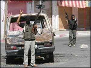 A Fatah gunman stands in front of a charred vehicle in Ga