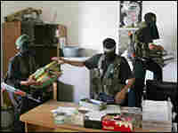 Masked members of the military wing of Hamas take files from an office after they captured the headq
