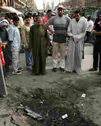 Iraqis inspect a crater left by an explosion at the site of a suicide car bomb attack