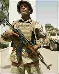 An Iraqi soldier mans a checkpoint in the restive Baghdad neighborhood of Yarmuk
