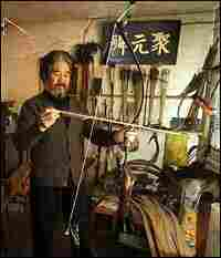 Yang Fuxi holds one of the bow-and-arrow sets he created at his workshop in Beijing.