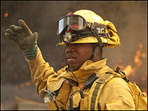 A Los Angeles City firefighter signals to his colleagues as a brush fire burns.