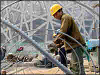 A Chinese construction worker works on steel bars at a construction site of the National Stadium.