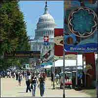 Capitol building looms over a Smithsonian exhibit on the National Mall.